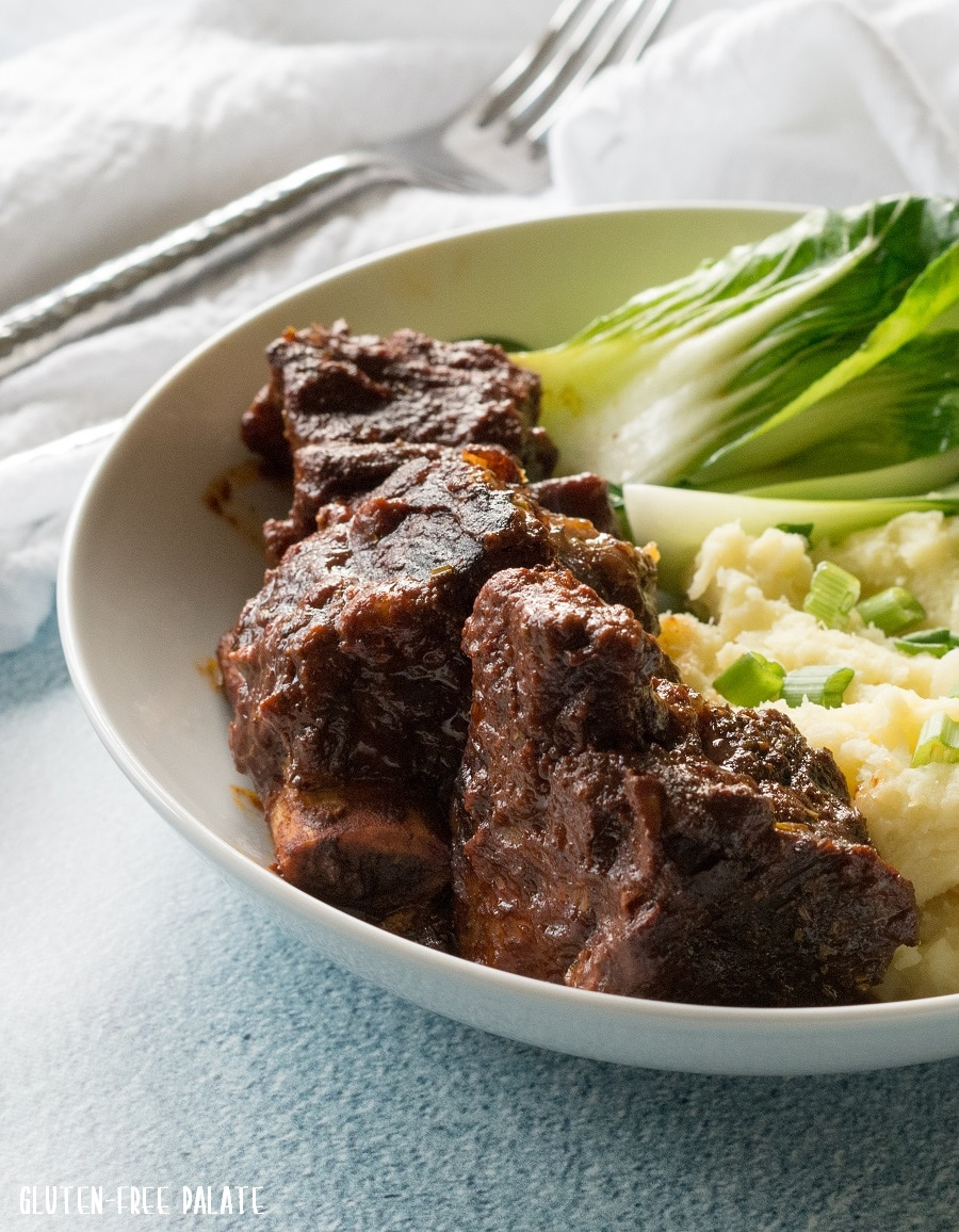 beef short rib, mashed pototoes, and greens on a white plate
