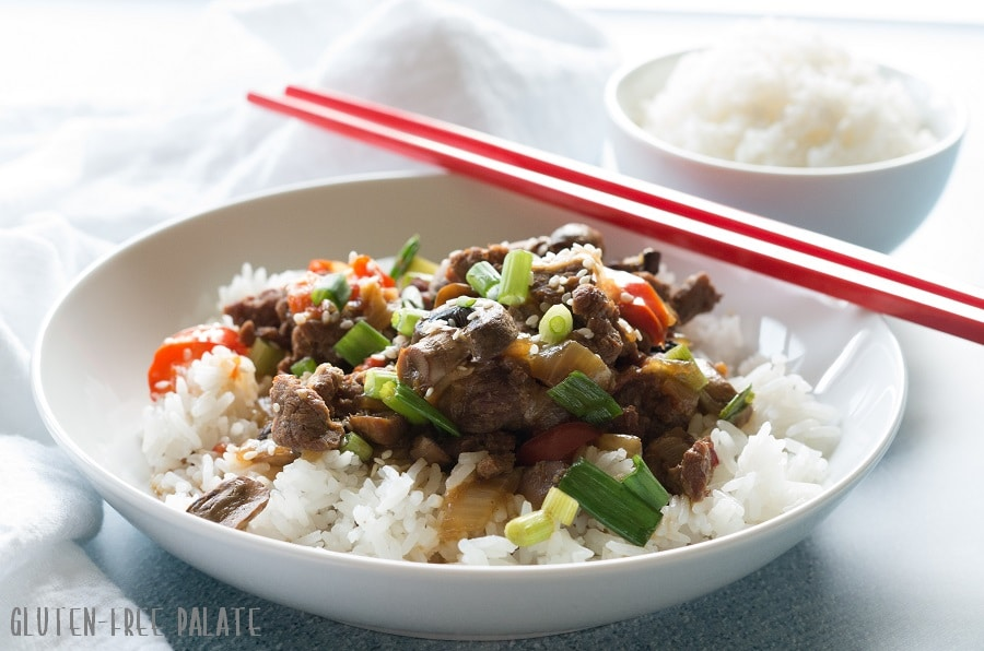 a side view of mongolian beef and vegetables over rice in a white bowl, red chopstick are resting on the side of the bowl