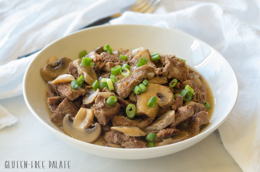 a side view of beef tips and mushrroms topped with sliced green onion on a white plate
