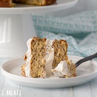 a close up of a slice of gluten free hummingbird cake on a white plate with a fork
