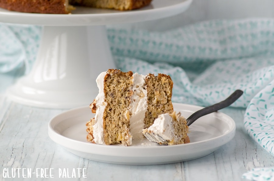 a slice of grain free hummingbird cake on a white plate with a fork with a bite out
