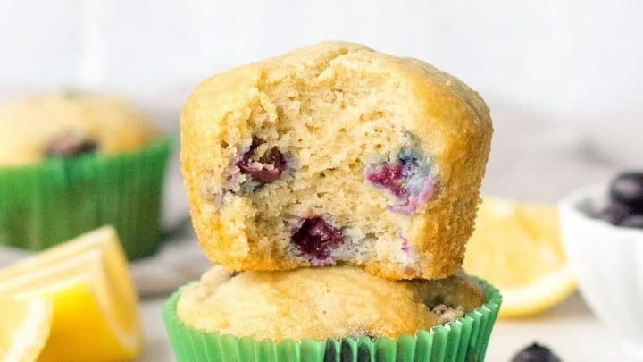 two stacked Paleo Blueberry Muffins with green wrappers