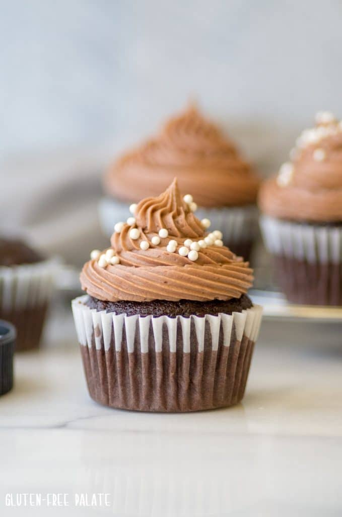 gluten-free chocolate cupcakes with chocolate frosting and white pearl sprinkles on top