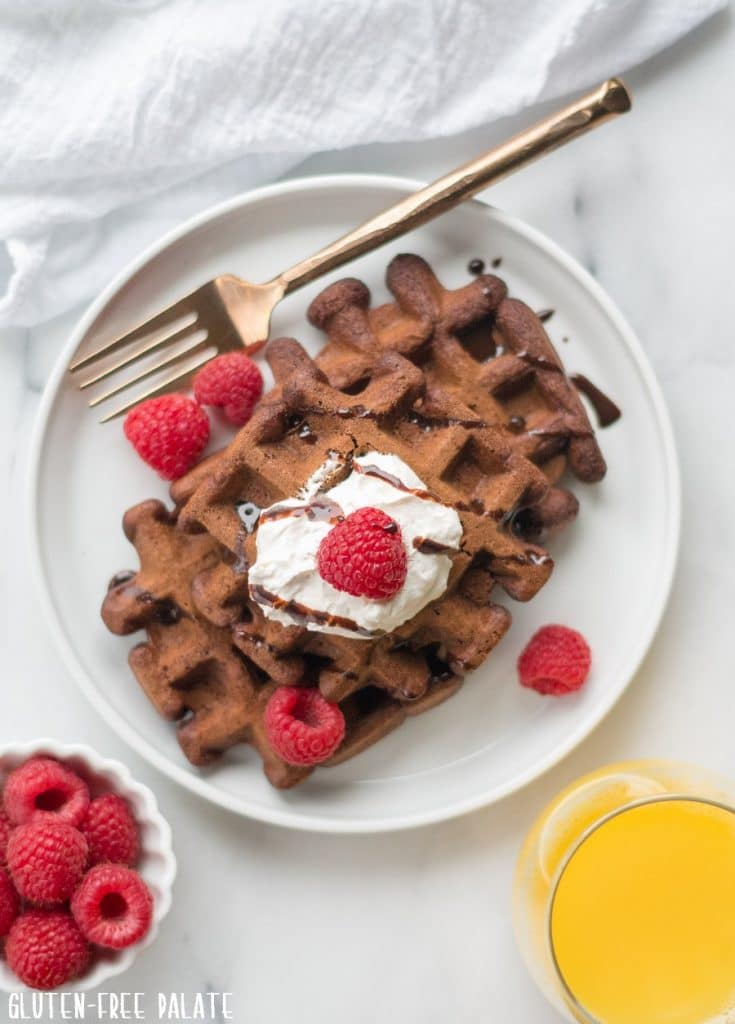 top down view of chocolate waffles on a white plate with raspberries next to a bowl of raspberries and a glass of orange juice