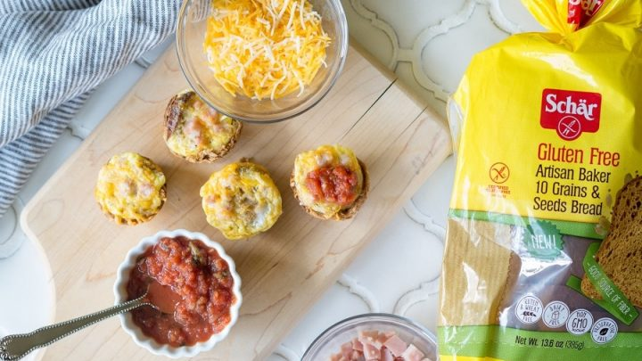 Mini Quiches on a cutting board next to a bowl of cheese and a bowl of chopped ham