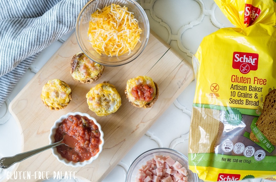 Mini Quiches on a cutting board with a bowl of cheese and a bowl of salsa with a spoon, next to a loaf of bread