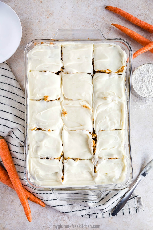 A glass pan with gluten-free carrot cake and white frosting, with carrots and a stripe napkin next to it