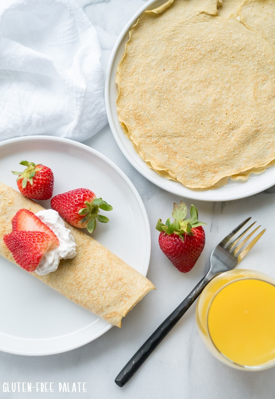 a crepe on a white plate, topped with whipped cream and strawberries next to a crepe and a glass of orange juice