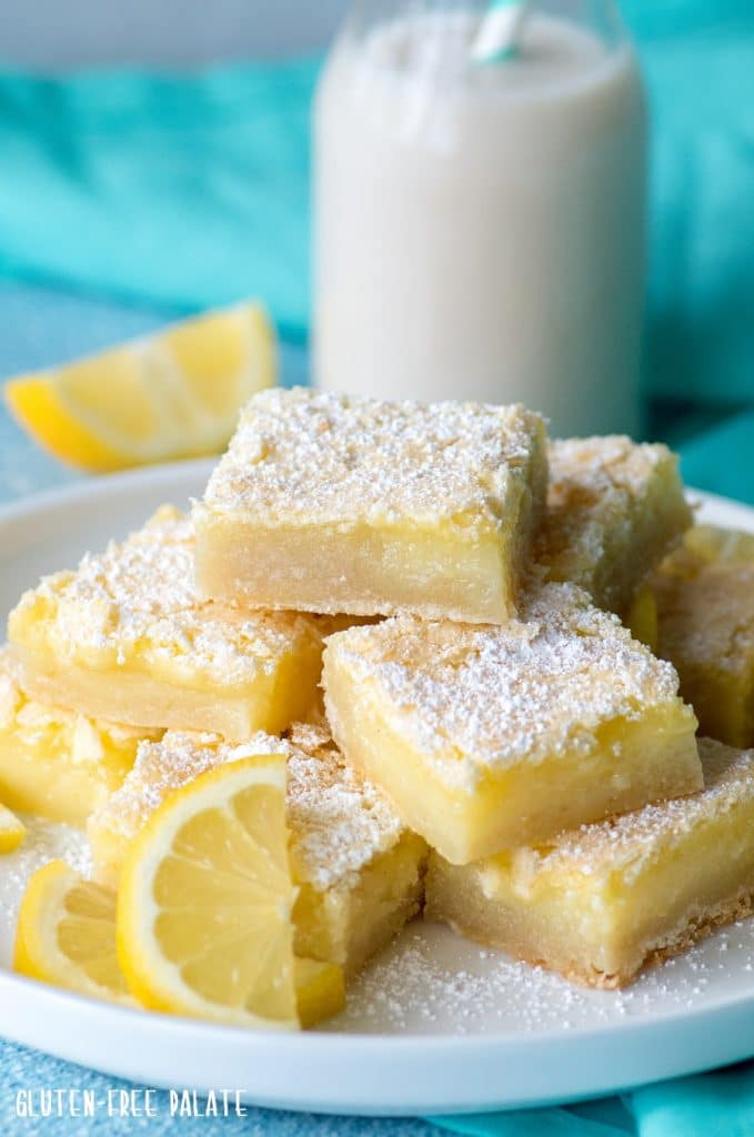 gluten free lemon bars stacked on a white plate with a jar of milk, a slice of lemon, and a blue napkin in the background