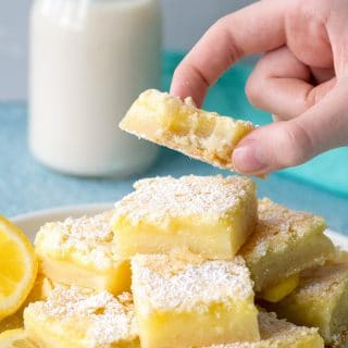 a hand holding a gluten free lemon bar with a bite out, over a plate of lemon bars