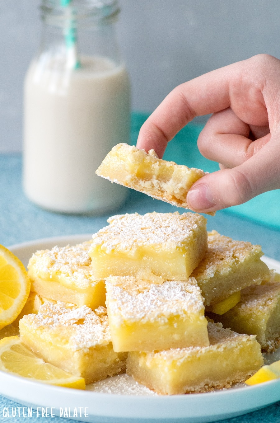 a hand holding a yellow lemon bar above a plate of lemon bars on a white plate