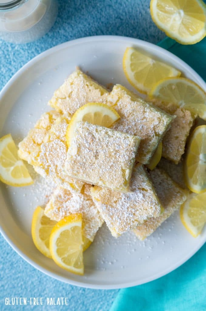 a top down view of lemon bars stacked on a white plate