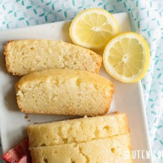 a close up of Gluten-Free Lemon Bread sliced on a white plate with slices of lemon on the side
