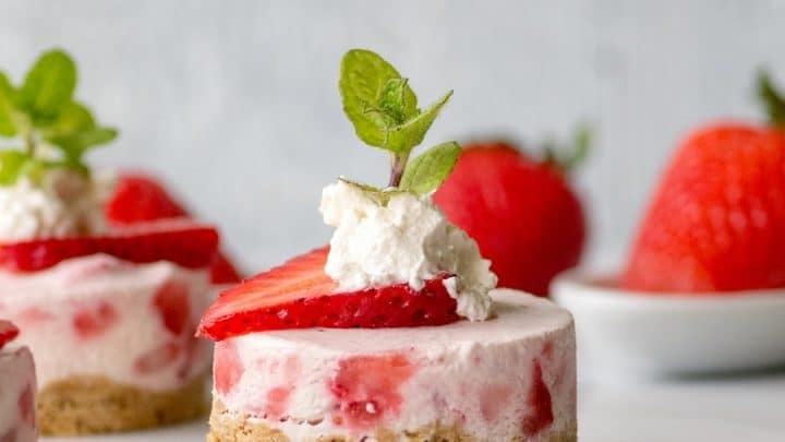a close up of a mini strawberry cheesecake with whipped cream and a mint leaf on top