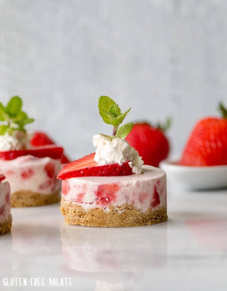 mini strawberry cheesecakes with whipped cream and a mint leaf on top