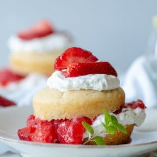 a close up of a Gluten-Free Strawberry Shortcake with whipped cream and sliced strawberries on a white plate with a spring on mint on the side