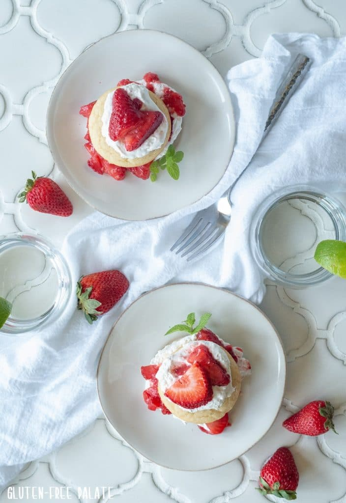 top down view of two a Gluten-Free Strawberry Shortcakes with whipped cream and sliced strawberries on white plates with a spring on mint on the side