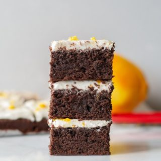 a close up of three brownies with white frosting and orange zest on top, stacked