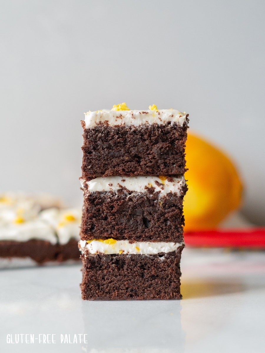 three brownies with white frosting and orange peel stacked with an orange in the background