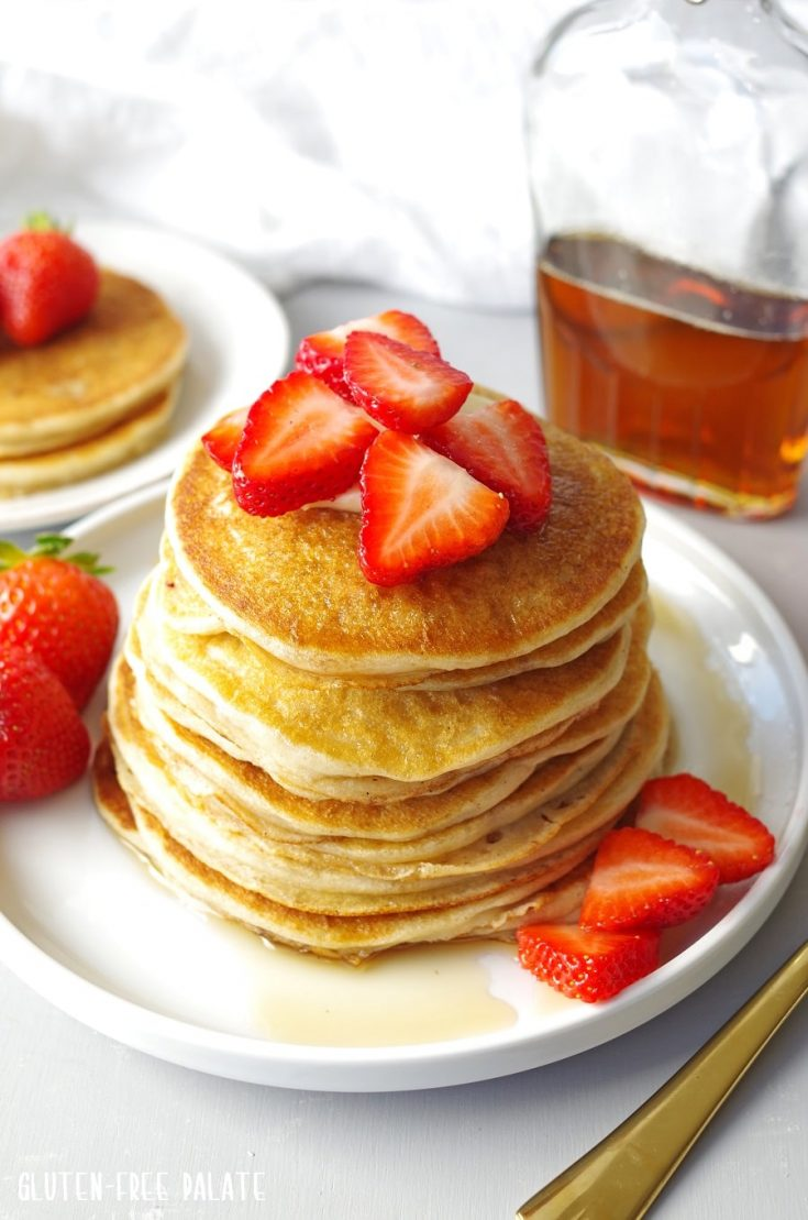 seven gluten free pancakes stacked on a white plate with strawberries on tip and a jar of maple syrup