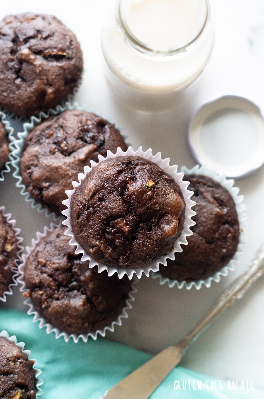 top down view of Grain-Free Chocolate Zucchini Muffins on a white background with a blue kitchen towl and a jar of milk