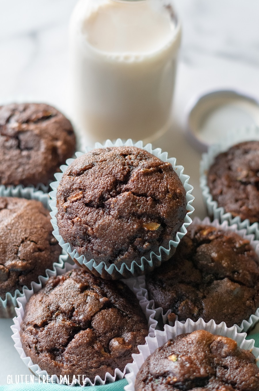 a close up of a chocolate muffin resting on top of other chocolate muffins