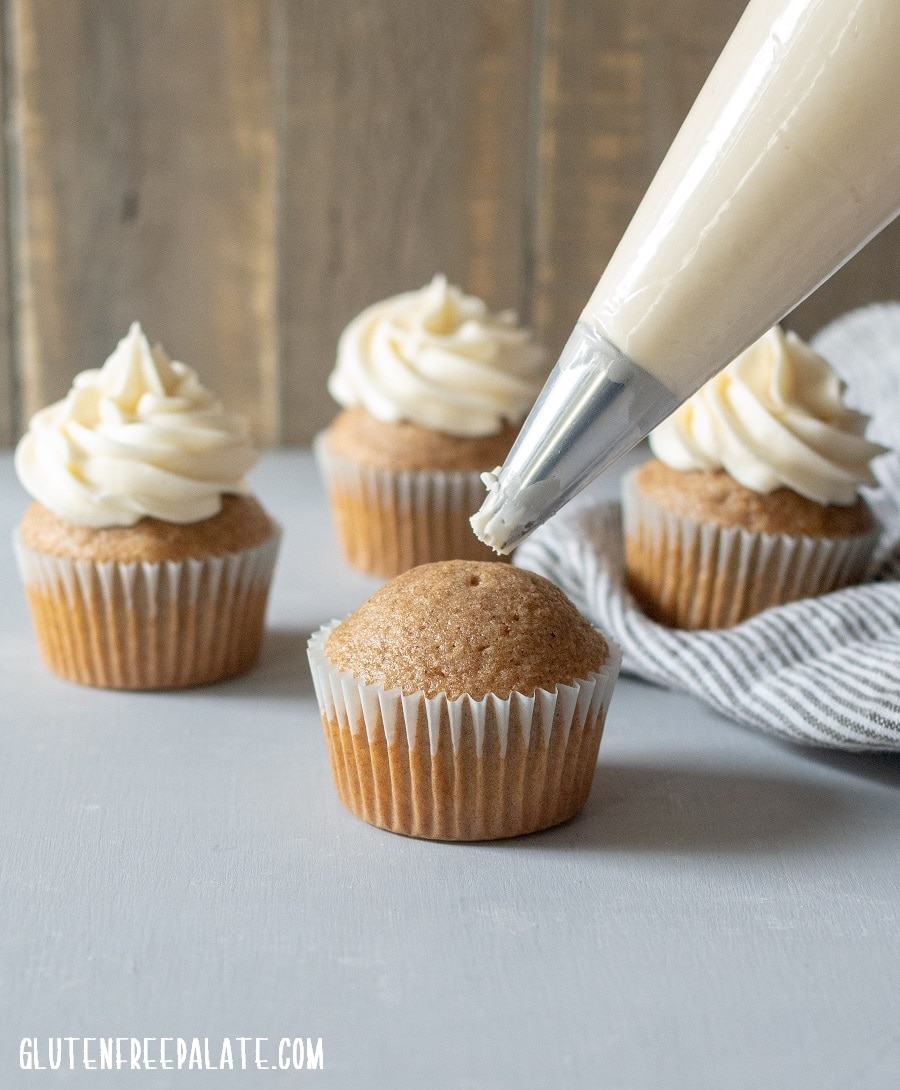 a chai cupcake with a piping bag, three chia cupcakes with frosting in the background