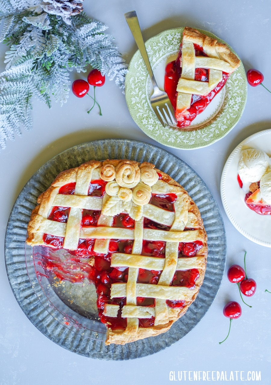 Gluten-free Cherry Pie on a tin plate next to two plates of slices of cherry pie