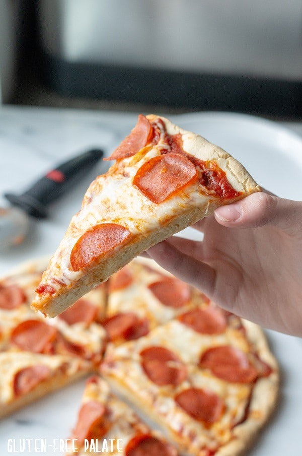 a hand holding a slice of gluten free pepperoni pizza