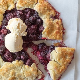 a close up of a blackberry tart on a piece of parchment paper with a slice cut out