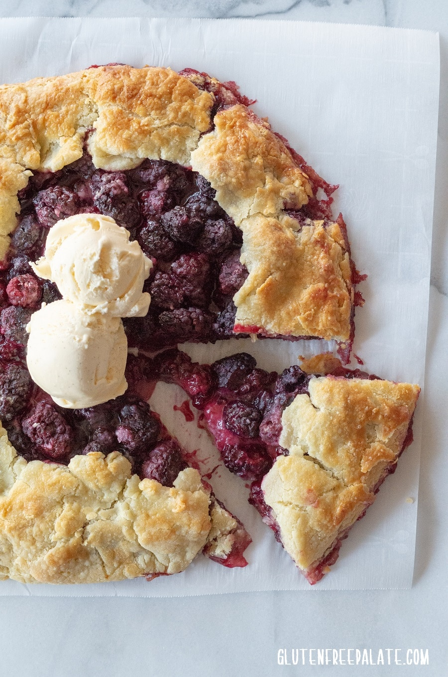 a blackberry tart on a piece of parchment paper with a slice cut out