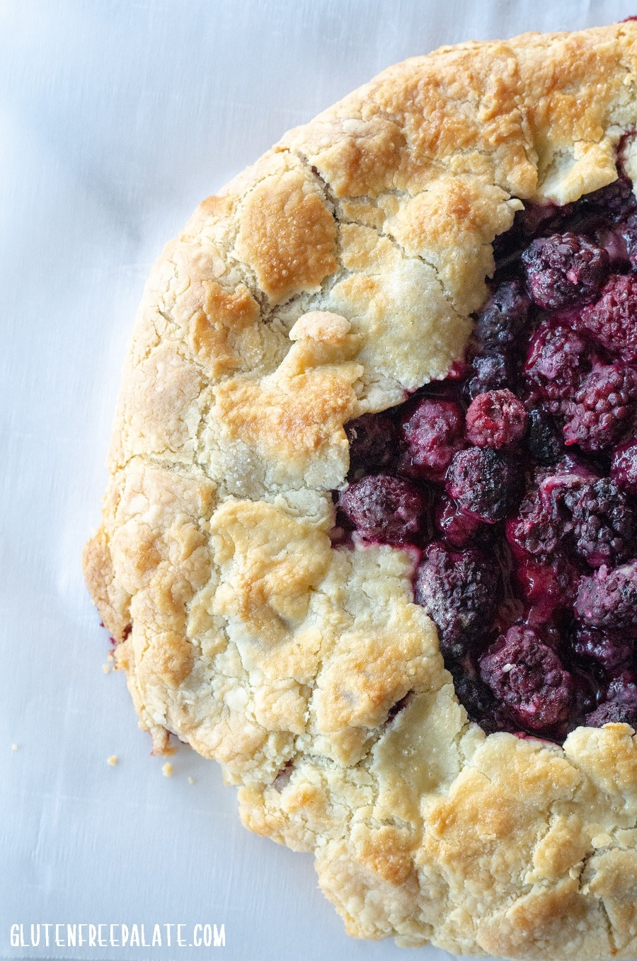 a close up of the side of a blackberry tart on a piece of parchment paper