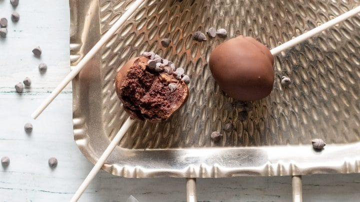 a close up of Gluten-Free Cake Pops covered in chocolate on a stick, on a metal tray