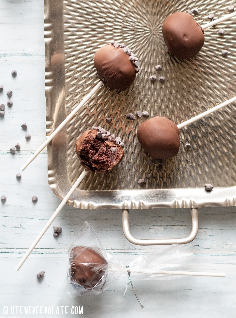 Gluten-Free Cake Pops covered in chocolate on a stick, on a metal tray