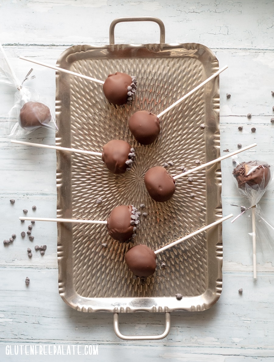 Gluten-Free Cake Pops covered in chocolate on a stick, on a metal tray, two are wrapped in plastic