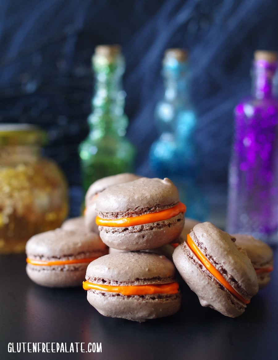 chocolate macaroons with orange filling stacked in front of collored glass bottles