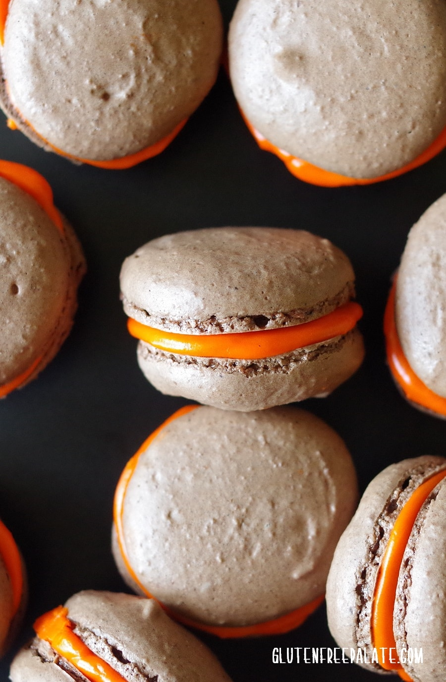 close up of chocolate macaroons with orange filling