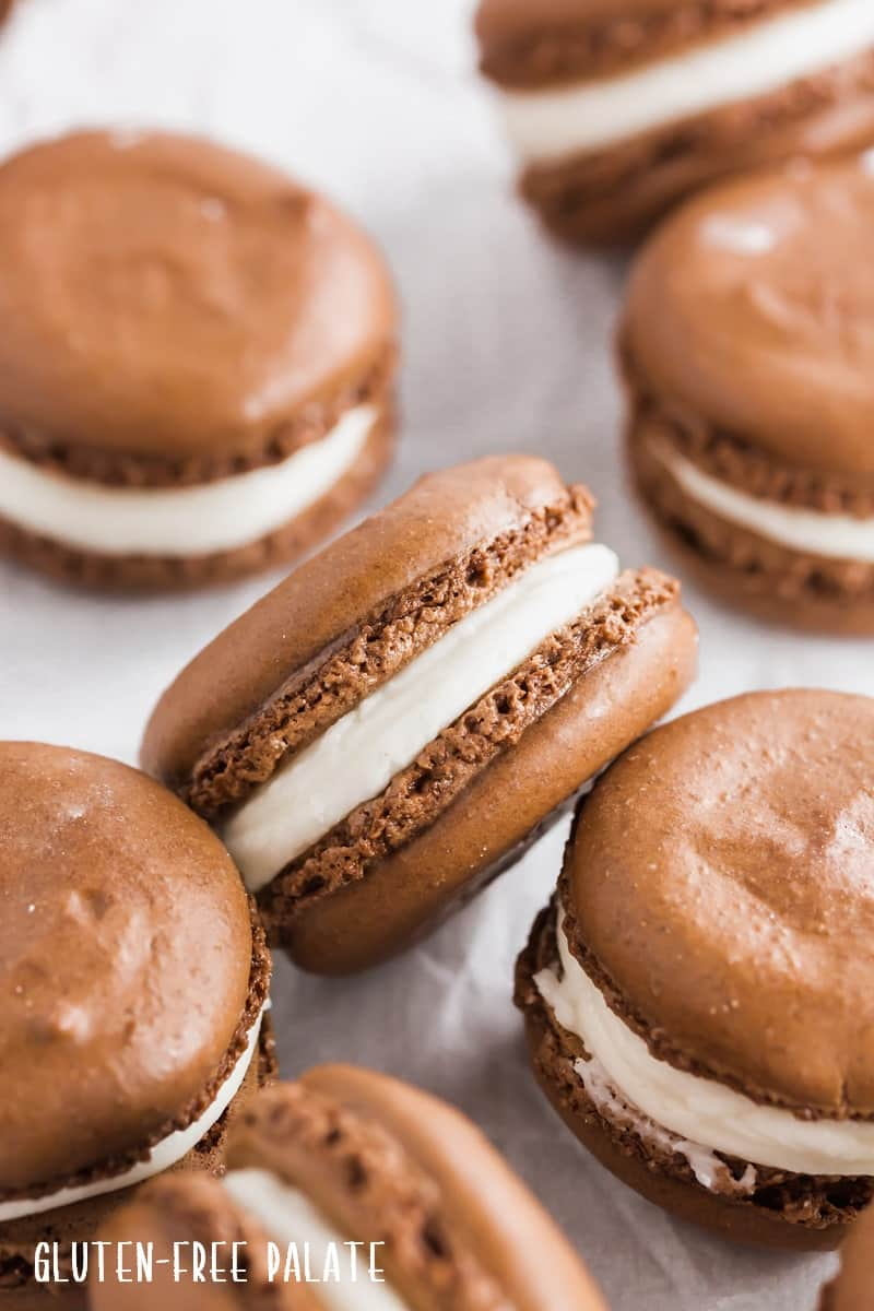 a side view of a gluten free chocolate macaron with white frosting in the center