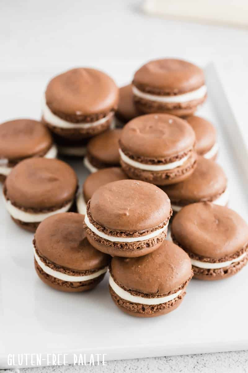 a stack of gluten free macarons with white frosting in the center
