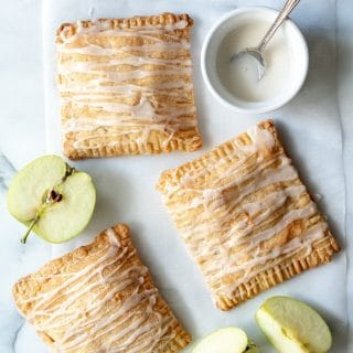 a close up of three apple turnovers with a glaze drizzled on top, next to slices of green apple