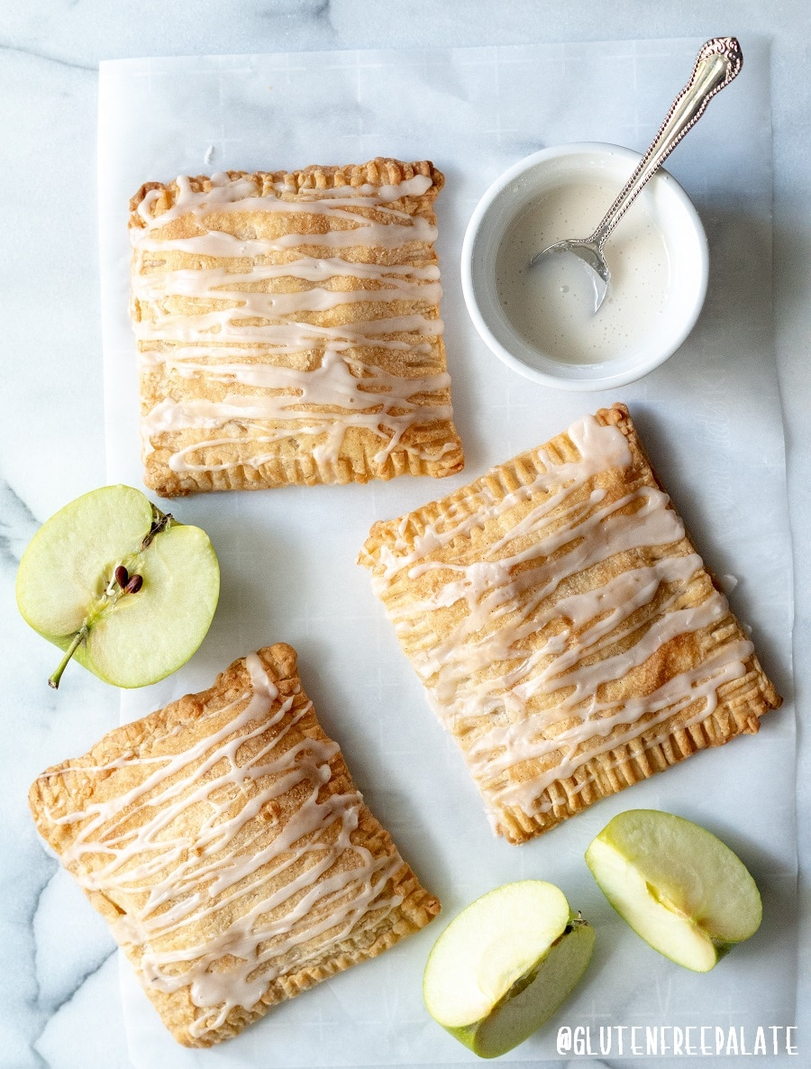 three apple turnovers with a glaze drizzled on top, next to slices of green apple