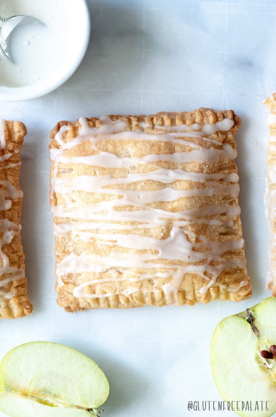 a close up of a apple turnover with a glaze drizzled on top, next to slices of green apple
