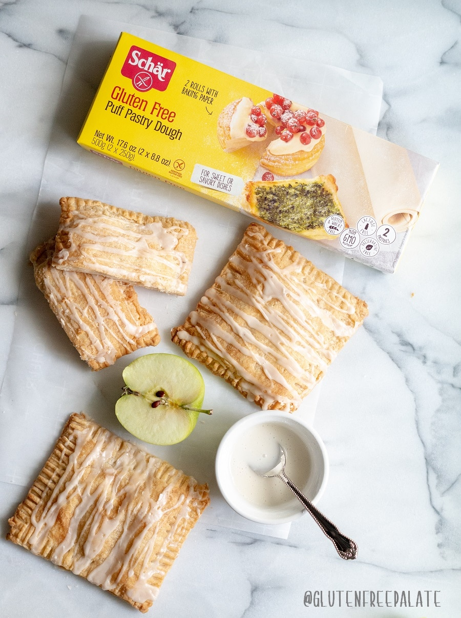 three apple turnovers with a glaze drizzled on top, next to slices of green apple and a box of schar frozen puff pastry