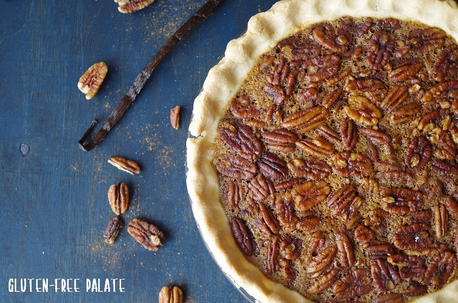 a round pecan pie on a blue background next to scatter pecans and a long vanilla bean
