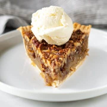 a slice of gluten free pecan pie topped with a scoop of vanilla ice cream