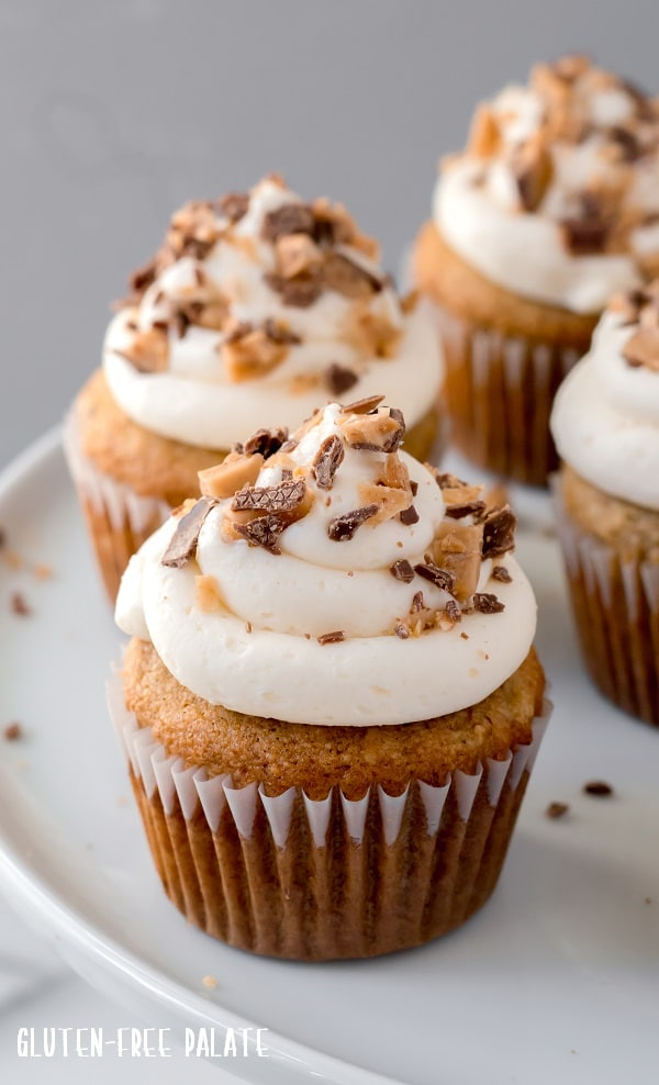 grain-free banana toffee cupcakes with white frosting and toffee on top