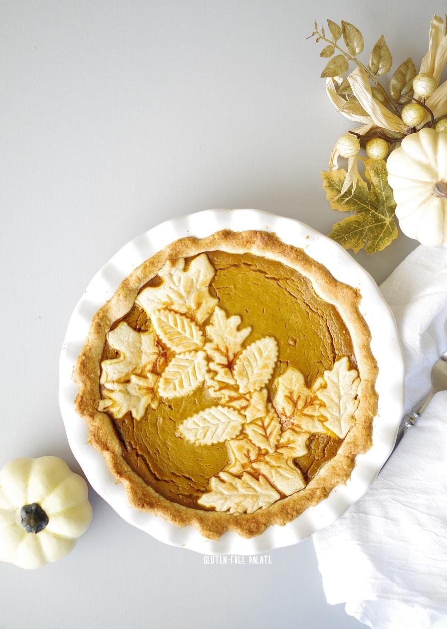 gluten free pumpkin pie in a white pie pan with white pumpkins and a white nampkin