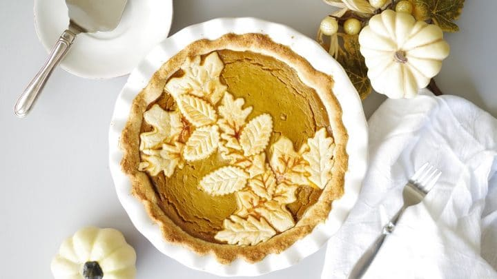 a close up of gluten free pumpkin pie in a white pie pan with white pumpkins and a white napkin