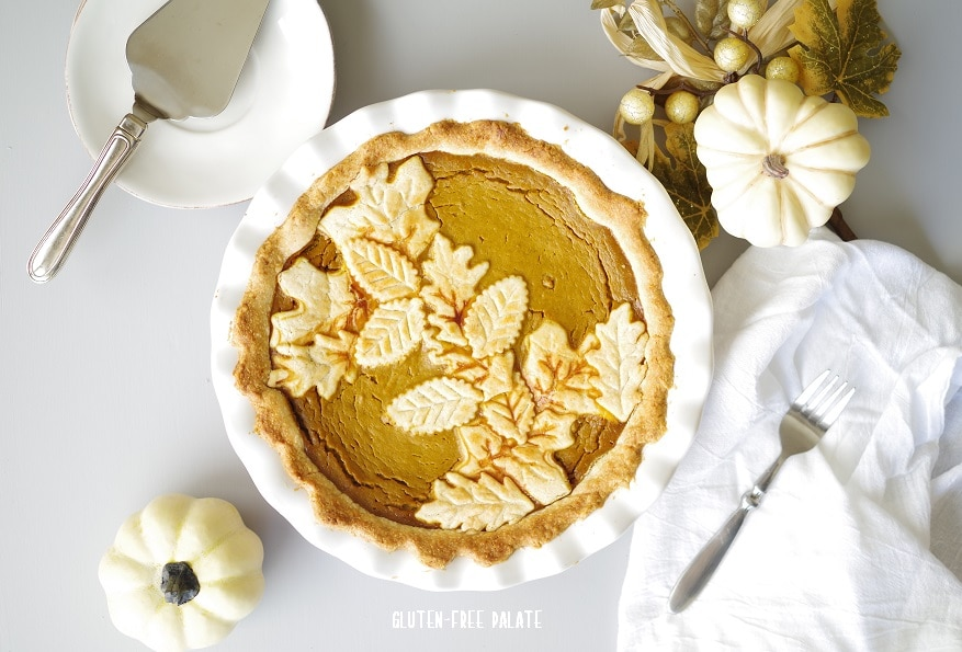 top down view of a pumpkin pie in a white pie pan, with decorated pastry leaves baked on top