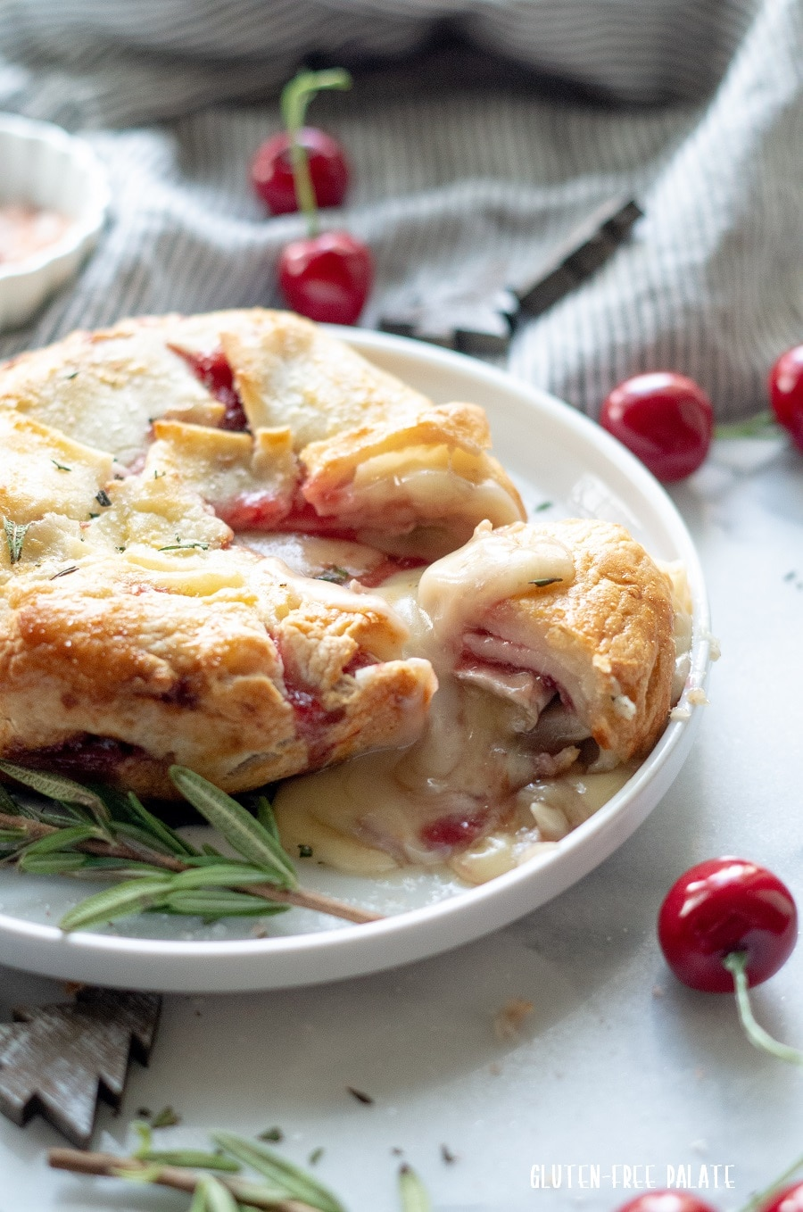 a side view of baked brie wrapped in puff pastry on a white plate with rosemary springs and cherries